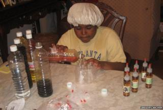 Leanna Archer sitting at a table mixing hair products, 2007