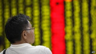 A Chinese investor looking at stock boards