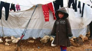 Syrian refugee standing outside a tent