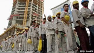Construction workers wait for a bus at the end of their work shift