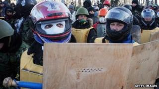 Protesters wield makeshift shields and wear motorcycle helmets in preparation for confrontation with riot police in Kiev on January 29, 2014