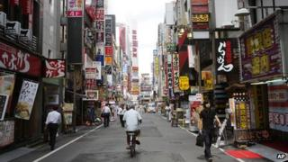 People walk along a street in a nightlife district in Tokyo on 4 September 2013.