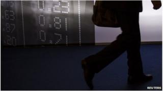 Man walks past board showing market data