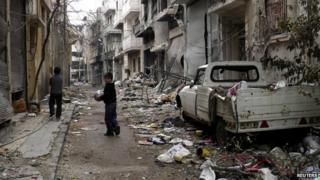 Children play along a street amid damaged buildings in the besieged area of Homs