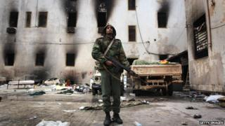 Opposition fighter guards a building in Benghazi