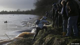 A woman climbing out of the way of the Severn Bore