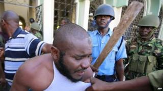 """A Muslim man is detained by police officers at the Masjid Mussa Mosque in Kenya""""s coastal town of Mombasa February 2, 2014."""