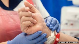 A nurse checks the pulse of a patient