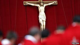 Priests stand in front of a crucifix. File photo