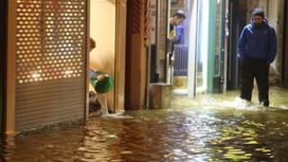 A woman bails out water from a shop as flood water rises in Cork city on Tuesday evening