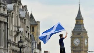 A Scotland football fan waves a Scottish flag near the UK Parliament