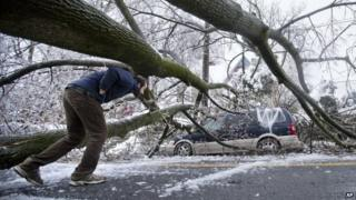 A man ducks under an ice covered downed tree that took out an utility line and landed atop a minivan, after a winter storm in Philadelphia 5 February 2014