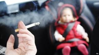 Person smoking in car with a small child in the back seat