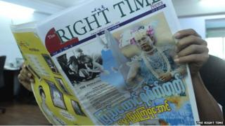 A man reads a copy of The Right Time newspaper with a doctored image of Myanmar leader Thein Sein on the cover