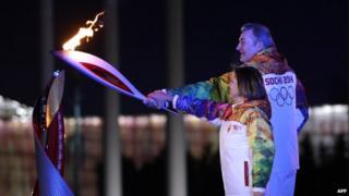 Russia's torchbearers Irina Rodnina and Vladislav Tretiak prepare to light the Olympic cauldron at the opening ceremony of the 2014 Winter Olympics on 7 February 2014, in Sochi.