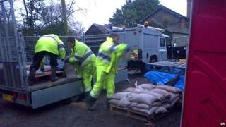 Workers take sandbags to Mordiford where the stream burst its banks