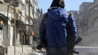 Syrian journalist carrying a camera and a weapon (9 February 2014)