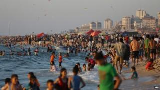 Palestinians are seen at the beach as the sun sets during a summer's day in Gaza City