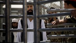 An Afghan prisoner waits in line for his release from Parwan Detention Facility after the US military gave control of its last detention facility to Afghan authorities in Bagram, on 25 March 2013.