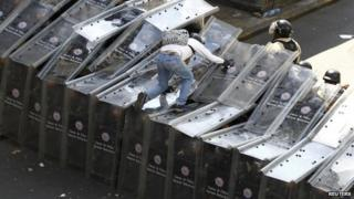 A demonstrator jumps on shield wall formed by riot police during a protest against the government in Caracas on 12 February, 2014