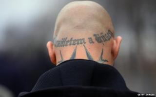 A skinhead with a tattoo of an SS slogan