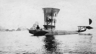 French seaplane moored off Sark coastline with man sitting on side of cockpit