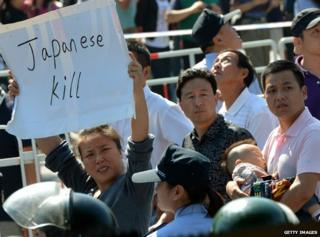 A woman holds up an anti-Japanese sign during a protest in September 2012