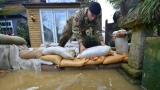 Handout photo issued by the Ministry of Defence of soldiers on Bridge Street, in Chertsey, placing sandbags around houses that are threatened with further flooding