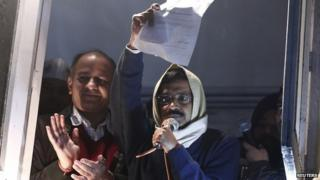 Arvind Kejriwal, chief of the Aam Aadmi Party, shows his resignation letter to his supporters as he quits as Delhi Chief Minister on 14 February 2014