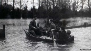 A boat navigates the floods in Wraysbury in 1947 to help deliver the milk