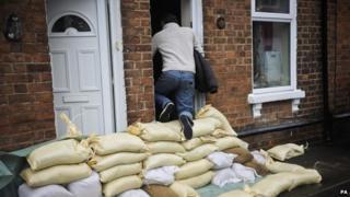 A local resident climbs over sandbags protecting houses on Alney Terrace, Gloucester.
