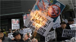 South Korean protesters burn anti-North Korea placards during a protest marking Kim Jong-il's birthday on February 16