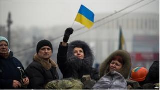 A woman waves a Ukrainian flag as demonstrators gather on a barricade in Kiev on February 9
