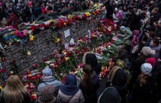People standing at a memorial covered in flowers in Independence Square