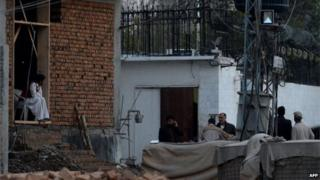 Pakistani security personnel gather outside the Iranian consulate following a suicide bomb attack in Peshawar on February on February 24, 2014.
