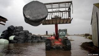 A farmer moves bales of animal feed at his flooded farm in Moorland, Somerset