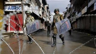 Government forces patrol a deserted street during a strike in Srinagar on Feb 11, 2014