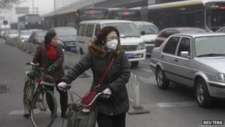 A cyclist wears an anti-pollution mask at a traffic junction on a busy street amid thick haze in Beijing on Tuesday
