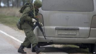 An unidentified gunman searches a vehicle while he and others block the road toward the military airport at the Black Sea port of Sevastopol