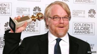 Philip Seymour Hoffman, hoisting a Golden Globe award for his role in Capote in 2006