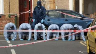 Forensic officers search at the site of a double murder investigation