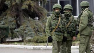 Unidentified armed men patrol in front of the airport in Simferopol, Ukraine, on 28 February 2014
