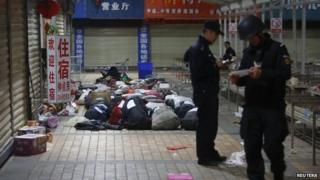 Policemen check unclaimed luggage at a square outside the Kunming railway station after a knife attack, in Kunming, Yunnan province, on 2 March 2014