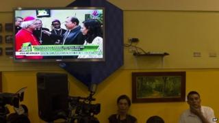 A TV screen shows live coverage of Nicaragua's President Daniel Ortega (centre) and his wife Rosario Murillo welcoming home Nicaragua's newly-appointed Cardinal Leopoldo Brenes