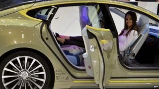 A woman poses inside the new Rinspeed XchangE concept car