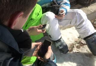 Three men in ski boots look at smartphones