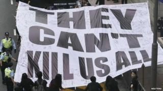"Demonstrators carry a banner that reads ""They can't kill us all"" during a march against violence on journalists in Hong Kong, 2 March 2014"