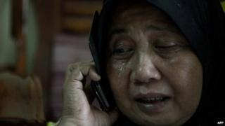 A relative of Norliakmar Hamid and Razahan Zamani, passengers on a missing Malaysia Airlines Boeing 777-200 plane, cries at their house in Kuala Lumpur on March 8, 2014. Malaysia and Vietnam on March 8 led a search for a Malaysia Airlines jet that has gone missing over Southeast Asia, as fears mounted over the fate of the 239 people aboard