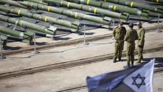 Israeli naval officers stand next to dozens of rockets
