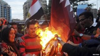 Egyptians burn the Qatar's flag outside its embassy in Cairo (30 November 2013)